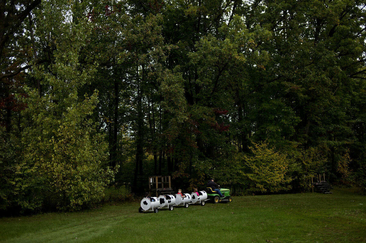 Children enjoy a riding lawnmower-pulled train during the Mills Township Fire Department's annual fire safety open house on Monday at the Mills Township Park Complex.