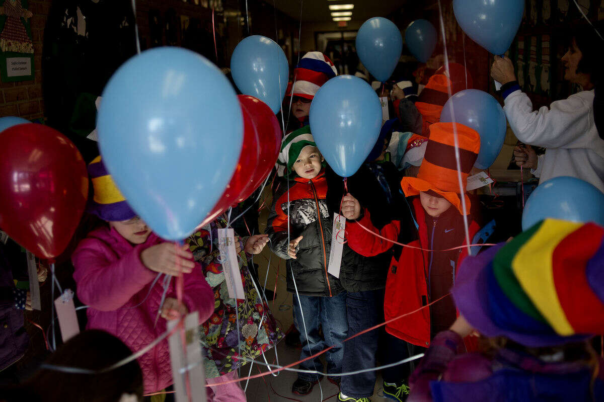 """First-grader Jeremiah Mobley, center, and the rest of his class get their Dr. Seuss """"Oh, The Places You'll Go"""" message balloons ready for a release outside of teacher Helen Gibbons' classroom on Monday at Adams Elementary School."""