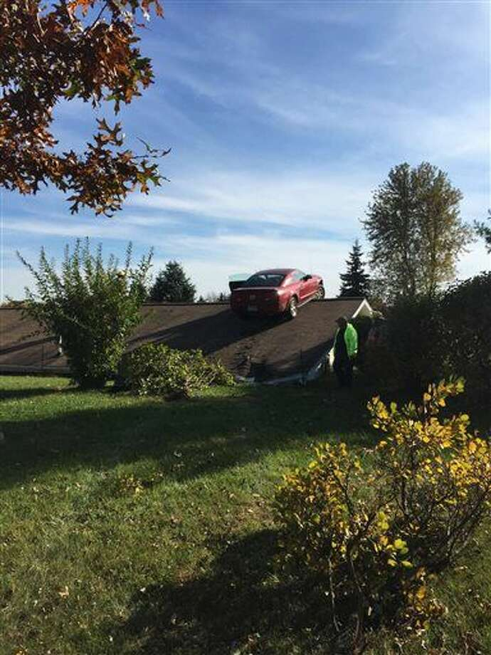 A Ford Mustang is shown on a roof of a house in Woodhull Township. State police say the driver had a medical problem and lost control of his car on Interstate 69 in Shiawassee County. Photo: Michigan State Police Via AP