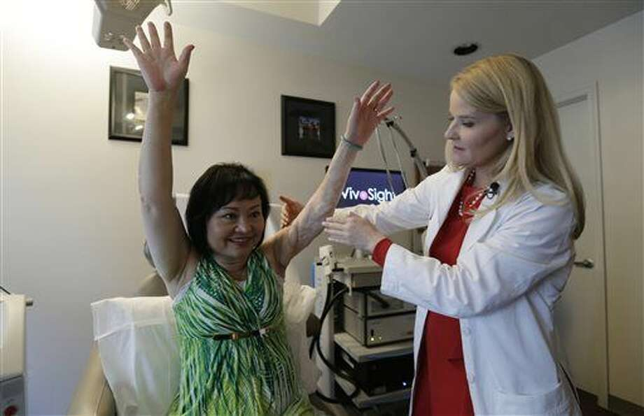 In this Sept. 26, 2015, photo, Dr. Jill Waibel examines Kim Phuc before the first of several laser treatments to reduce pain and the appearance of burn scars in her back and left arm in Miami. Phuc was injured by a napalm bomb in Vietnam 40 years ago. (AP Photo/Nick Ut) Photo: Nick Ut