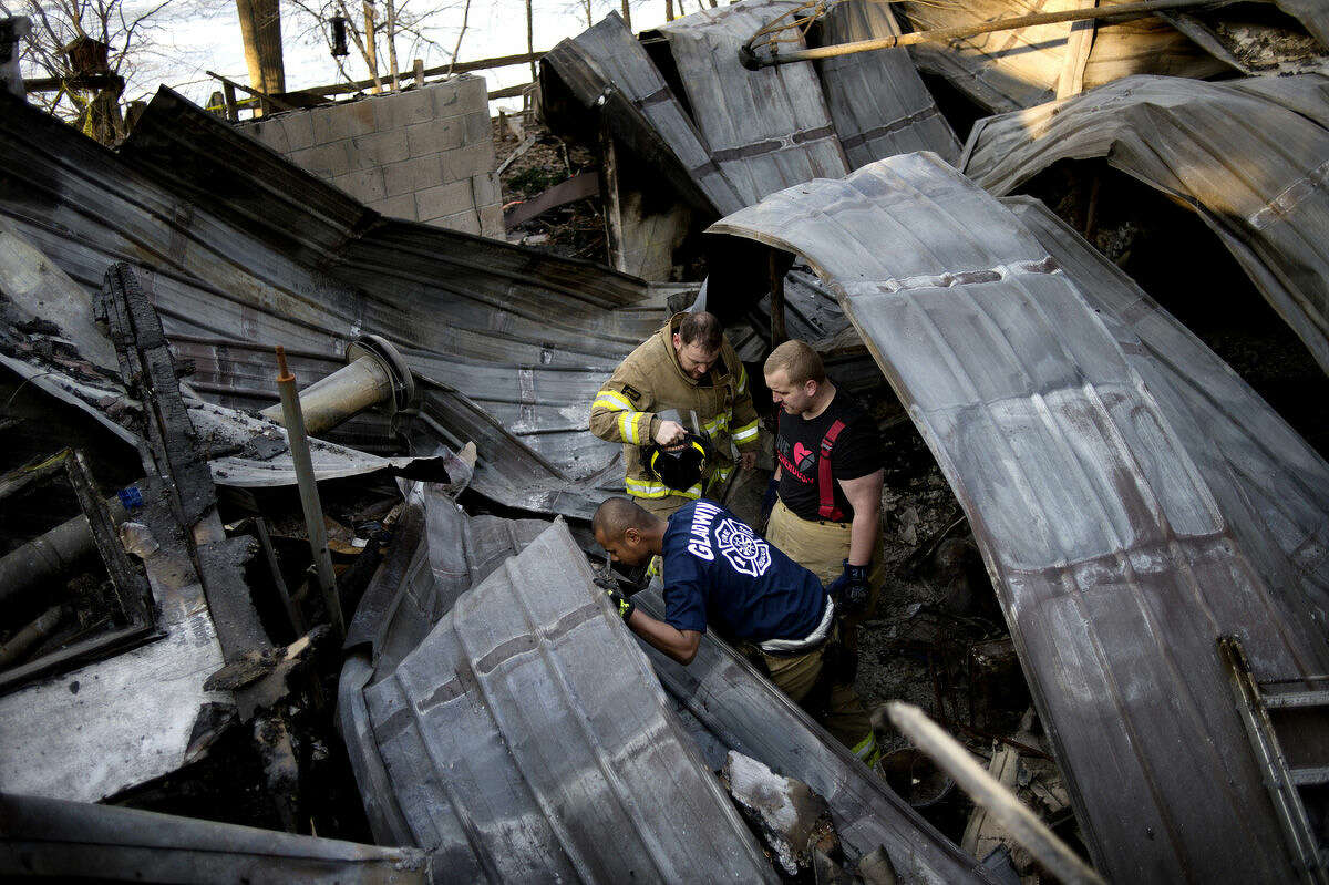 Clockwise, starting at bottom, Gladwin Rural-Urban Fire Department firefighters VJ Seng, Travis Povey and Dale Carper look for Carper's helmet among the rubble at 1717 E. Pratt Lake Road. Carper lost the helmet while the three were trapped for an hour under the debris while fighting the fire on Feb. 19.