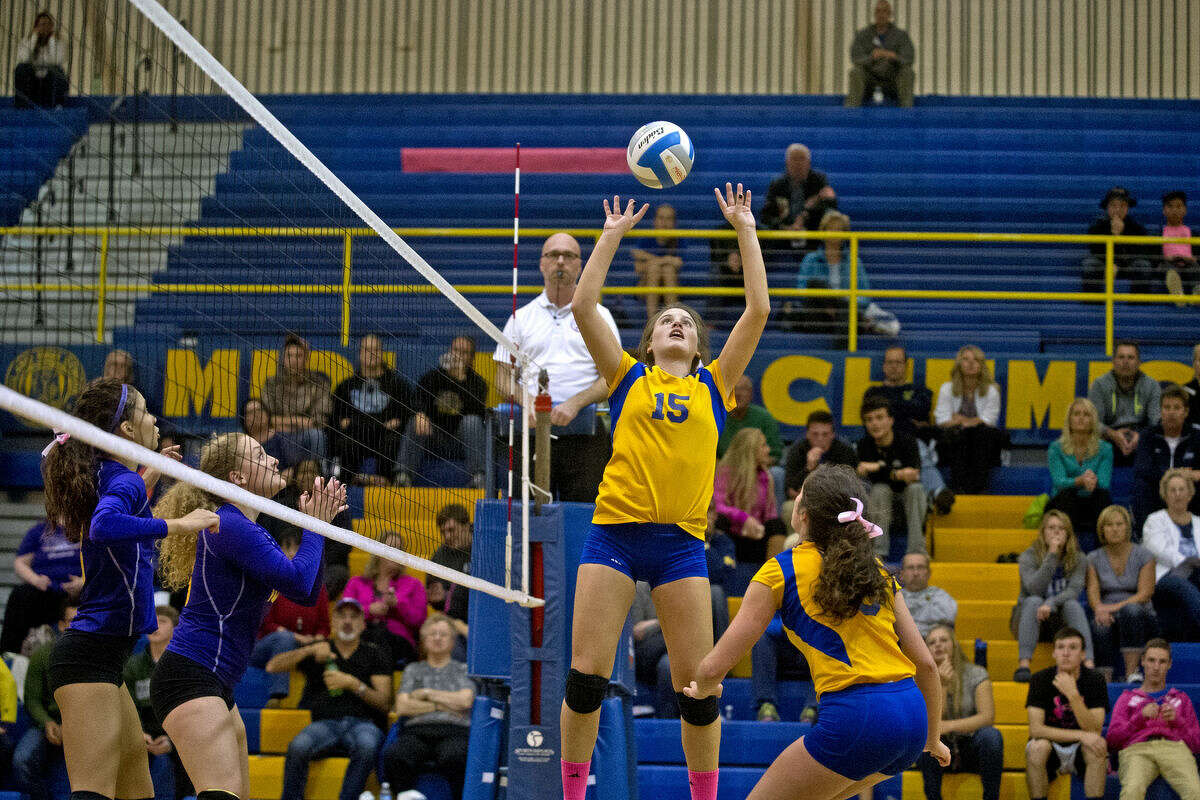 Midland's Emma Wolf, center, sets the ball as teammate Haley Sisitki watches while Bay City Central's Stephanie Reed and Audrey Kopec wait during the first set on Tuesday at Midland High School. The Chemics defeated the Wolves in all three sets to win the match.