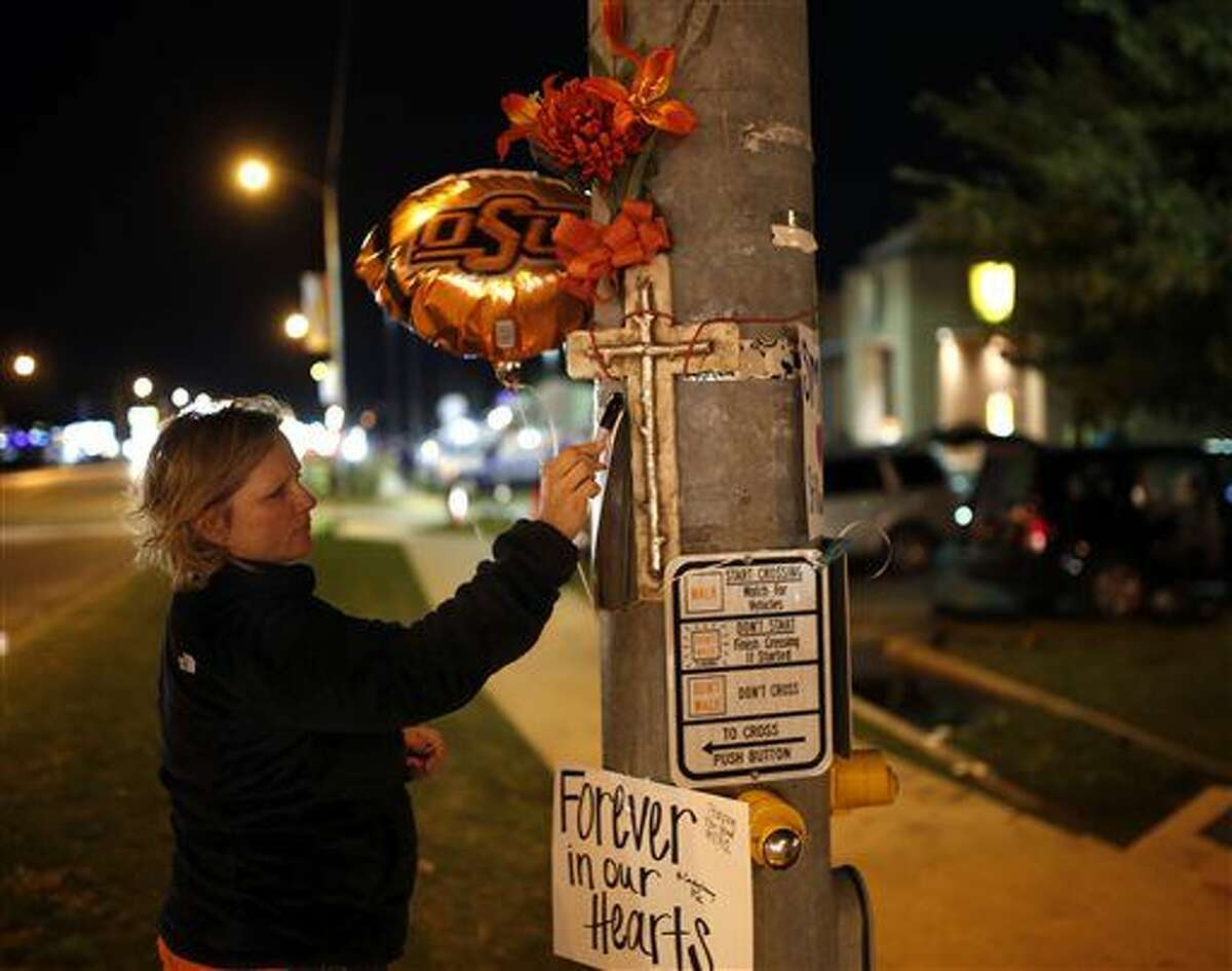 Teria Frank writes a message on a sign at a memorial in Stillwater, Okla., Saturday, Oct. 24, 2015, near where a car crashed into spectators during the Oklahoma State University homecoming parade killing multiple and injuring several others. (Sarah Phipps/The Oklahoman via AP)