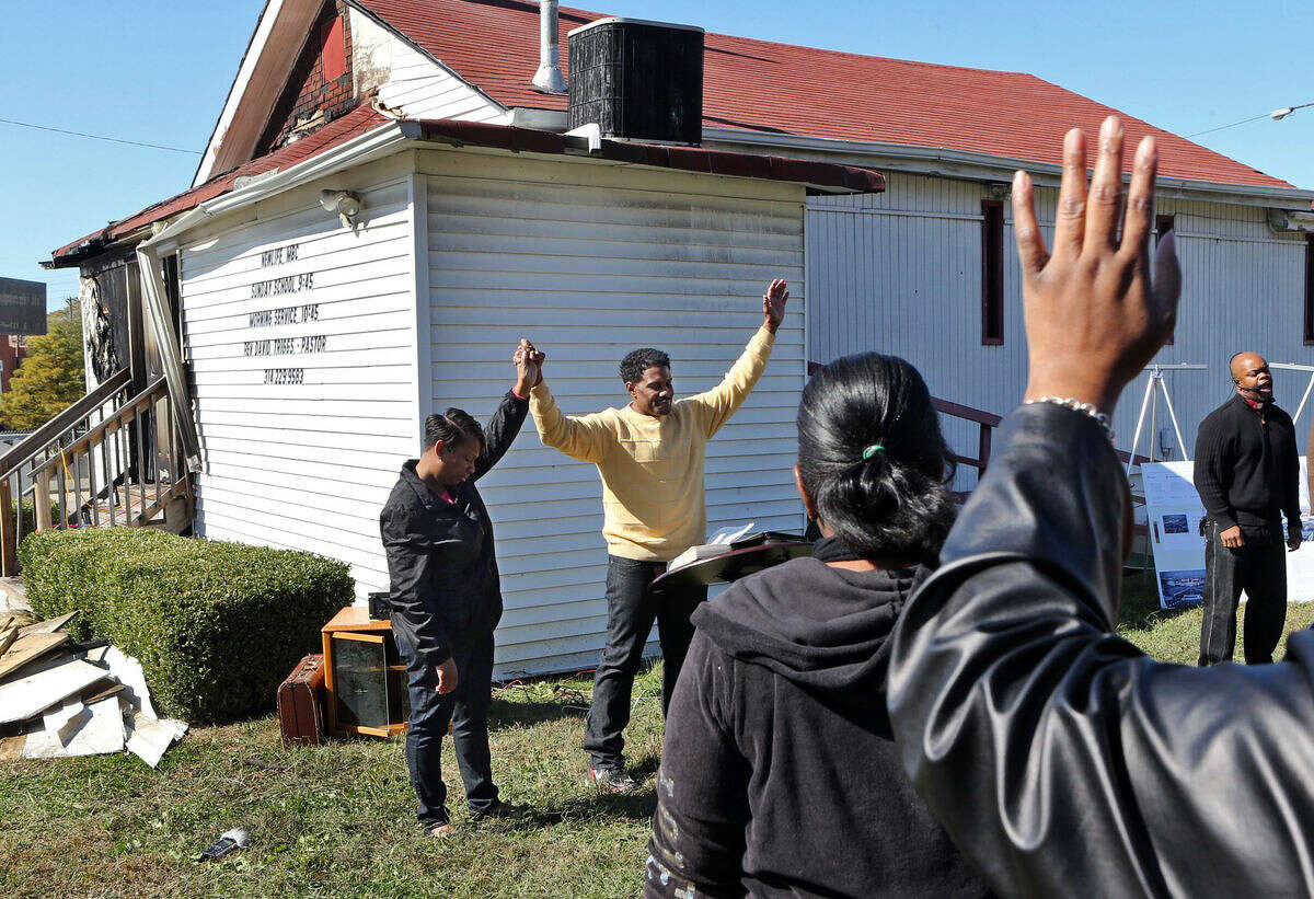 FILE - In this Oct. 18, 2015 file photo, Pastor David Triggs and his wife, Charronda, hold hands during an outdoor service following a fire at the church at the New Life Missionary Baptist Church in St. Louis. Authorities announced Friday, Oct. 30, 2015 the arrest of a 35-year-old black man suspected of setting fires at several predominantly African-American St. Louis-area churches that spurred a hate-crime investigation.