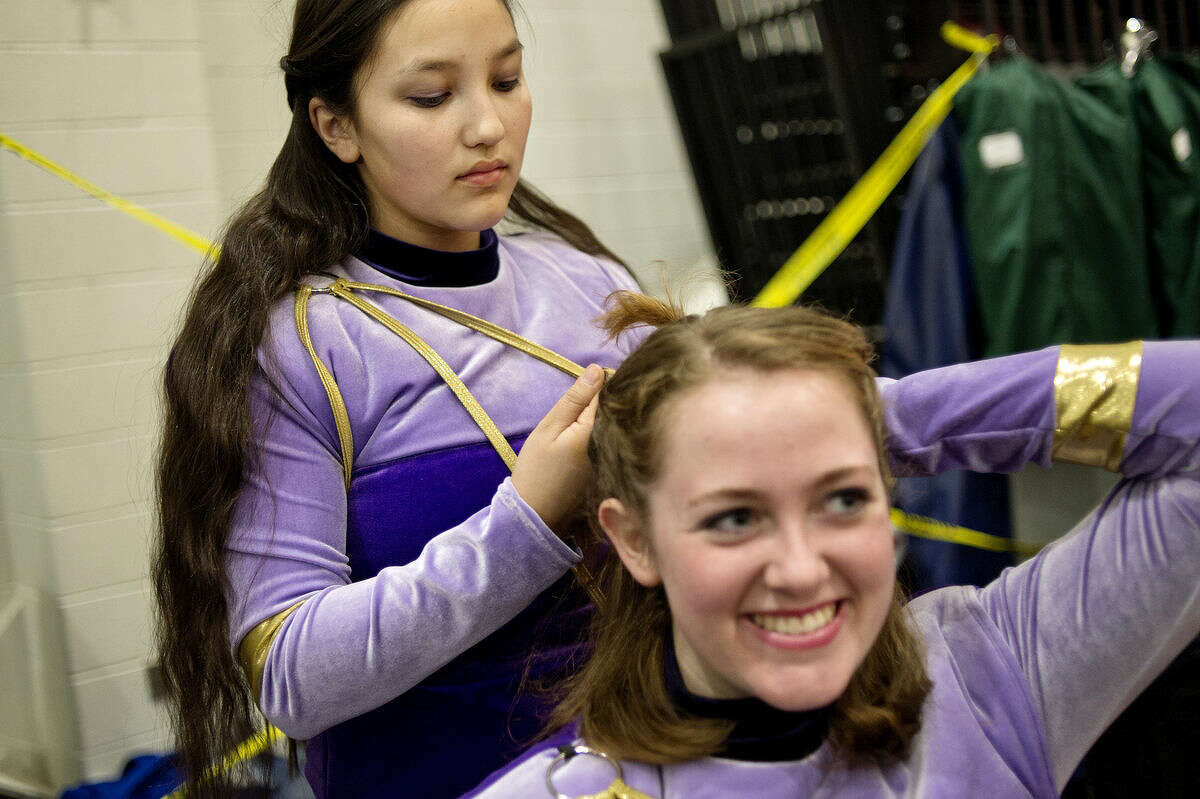 Anna Koh, left, fixes the hair of fellow sophomore and Farmington Hills United Percussion Ensemble member Carly Smith backstage before their performance at the 40th Annual Michigan Color Guard Circuit Championships on Sunday at the SVSU Ryder Center. More than 120 Michigan and Canadian high school color guard and winds and percussion teams competed for judges and spectators over Saturday and Sunday event. Teams were judged based on criterion including, musicianship, execution, design, choreography and acrobatics, to name a few.