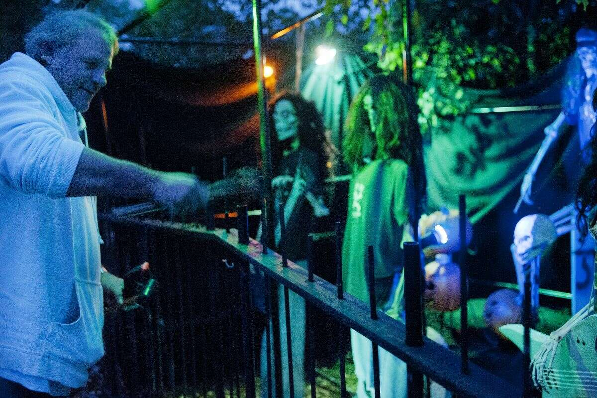 Scott Schaffer of Midland finishes assembling a skeleton band in his front yard to go with the rest of his Halloween decorations.