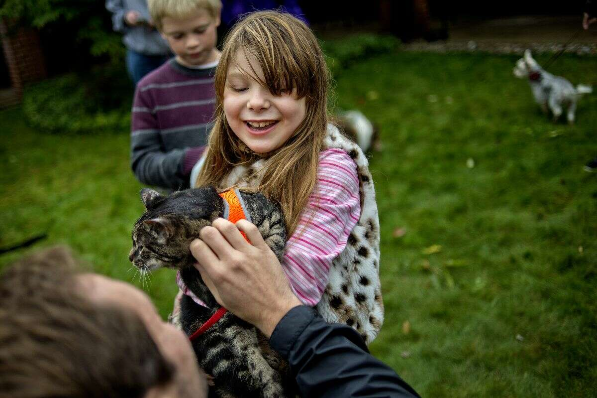 Lily Goniea, 8, presents her cat Rorschach to Rector Ken Hitch for a blessing during St. Francis Day with the Blessing of the Animals on Sunday at St. John's Episcopal Church.