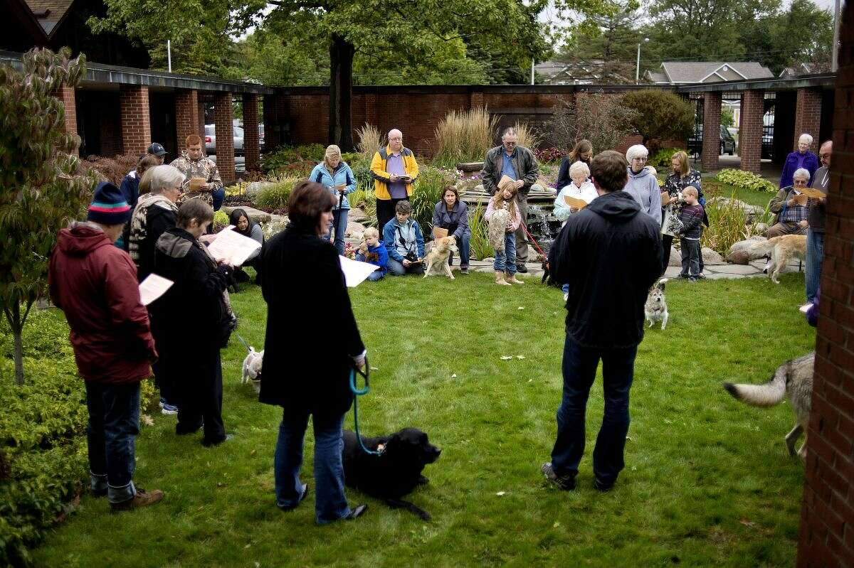 Guests gather with their pets in the courtyard during St. Francis Day with the Blessing of the Animals on Sunday at St. John's Episcopal Church.