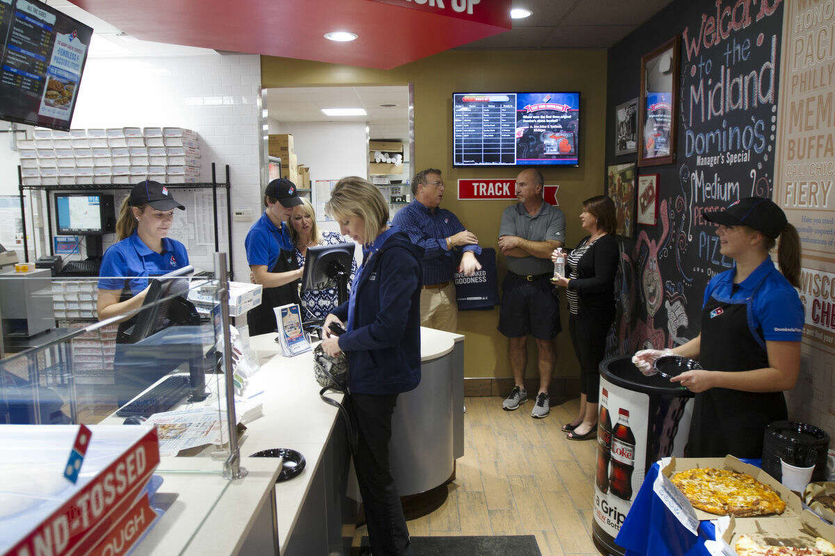 Diane Butler, director of membership development for the Midland Area Chamber of Commerce, center, orders some pizzas at the new Domino's.