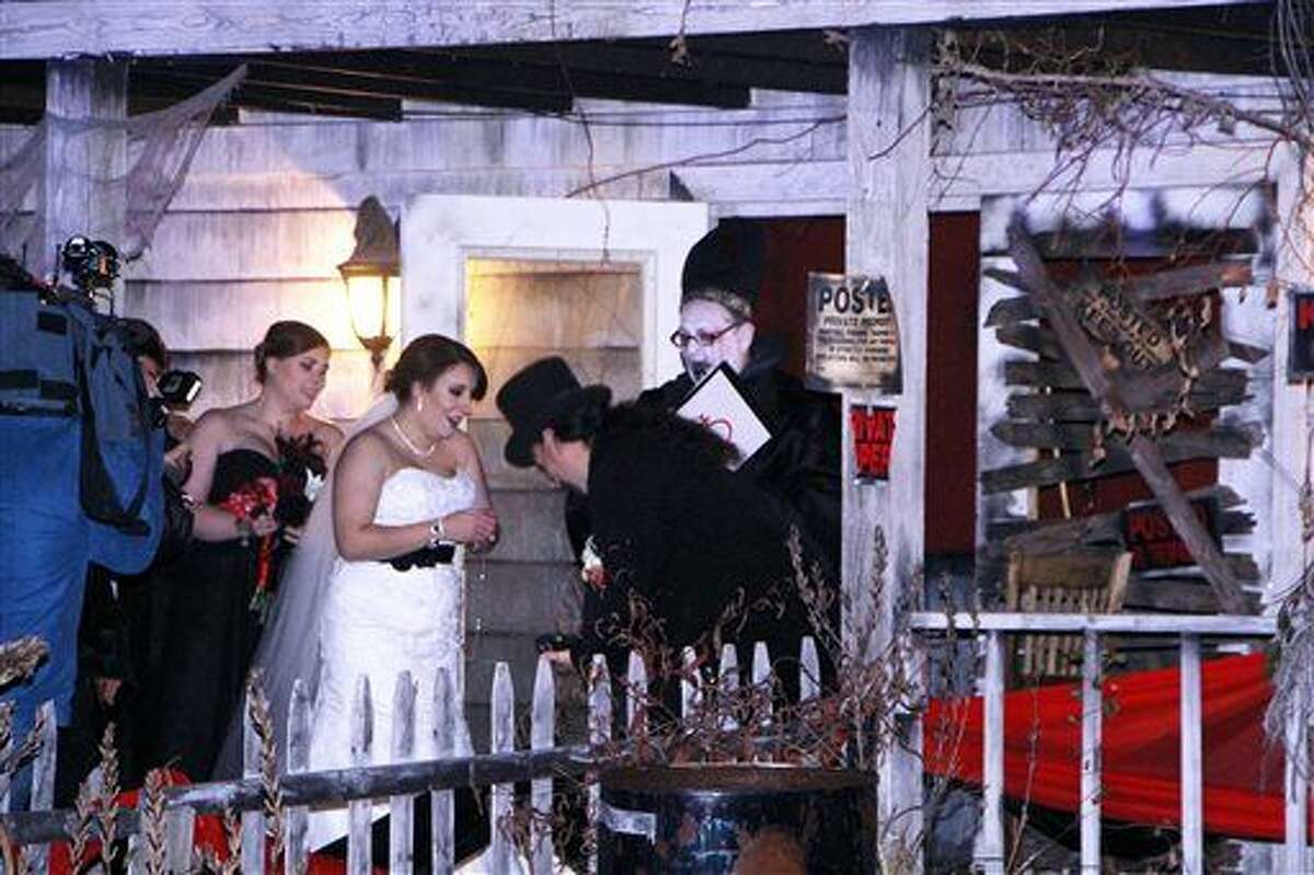 """Melissa Cote and Tom Cowen, who both work at Spooky World Presents Nightmare New England in Litchfield, N.H., were married the night of Monday in front of the attraction's haunted house. During the ceremony, the justice of the peace encouraged them to """"haunt and howl at the moon together as long as you shall live,"""" and """"to have and to hold from this night on, in madness and in haunting fun."""""""