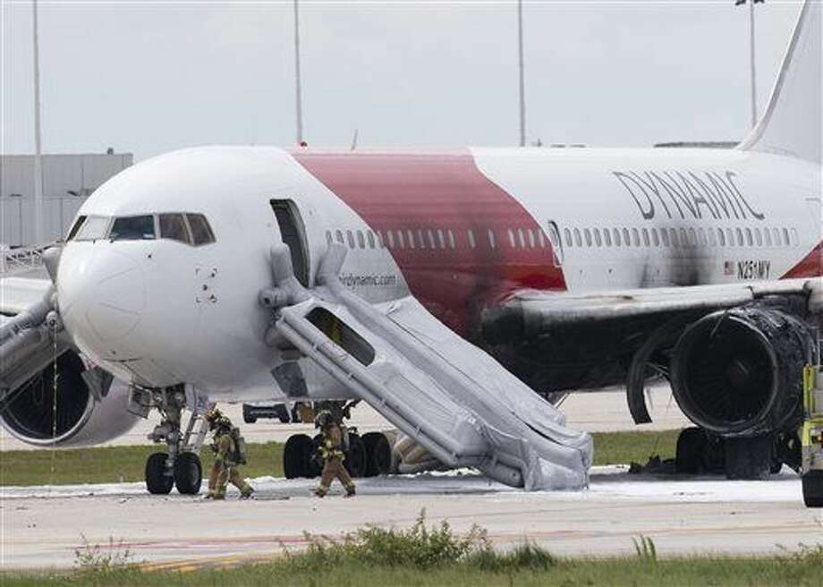 Firefighters walk past a Dynamic Airways Boeing 767, Thursday, Oct. 29, 2015, at Fort Lauderdale/Hollywood International Airport in Dania Beach, Fla. The passenger planes' engine caught fire Thursday as it prepared for takeoff, and passengers had to quickly evacuate on the runway using emergency slides, officials said. The plane was headed to Caracas, Venezuela. (AP Photo/Wilfredo Lee) Photo: Wilfredo Lee