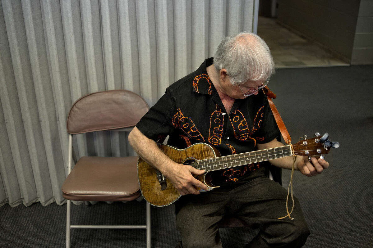 """Leslie VanWormer, of Midland, tunes up his baritone ukulele during the Winter Ain't Stopping Serious Uke Players (WASSUP!) ukulele festival on Saturday. """"It's a learning experience and fun,"""" said VanWormer of the event."""