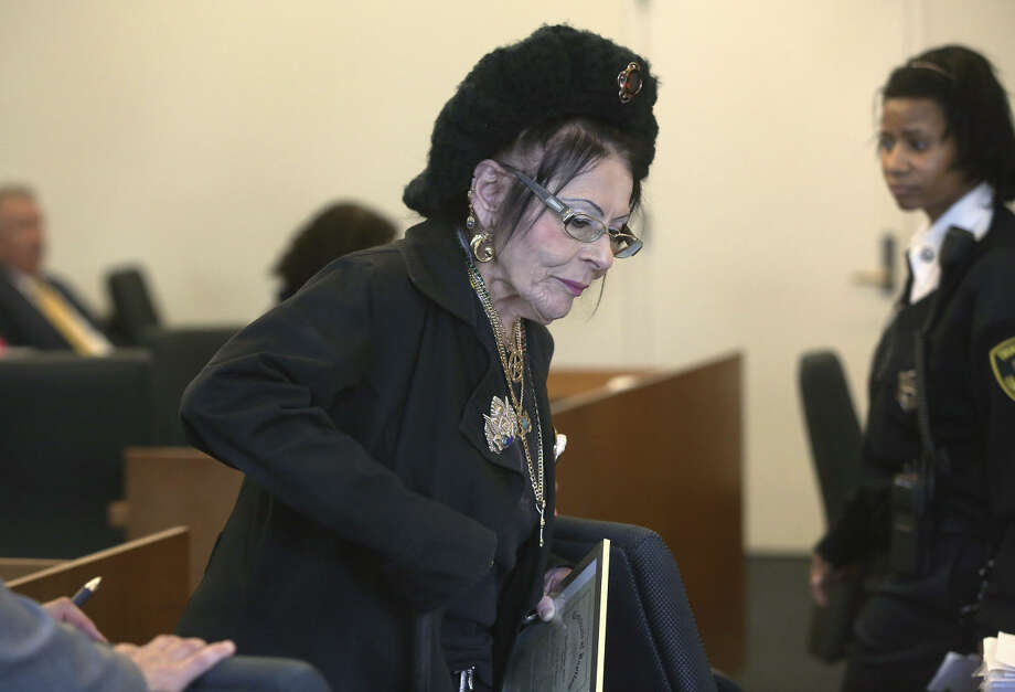 Witch priestess Lori Sforza holds a certificate of baptism as she returns to her seat after testifying in district court Wednesday, Oct. 28, 2015, in Salem, Mass. Sforza was seeking a restraining order against self-described warlock Christian Day, who she claimed harassed her during the past three years over the phone and on social media. The judge granted a protective order against Day, who said he would appeal the ruling. (Pat Greenhouse/The Boston Globe via AP, Pool) Photo: Pat Greenhouse