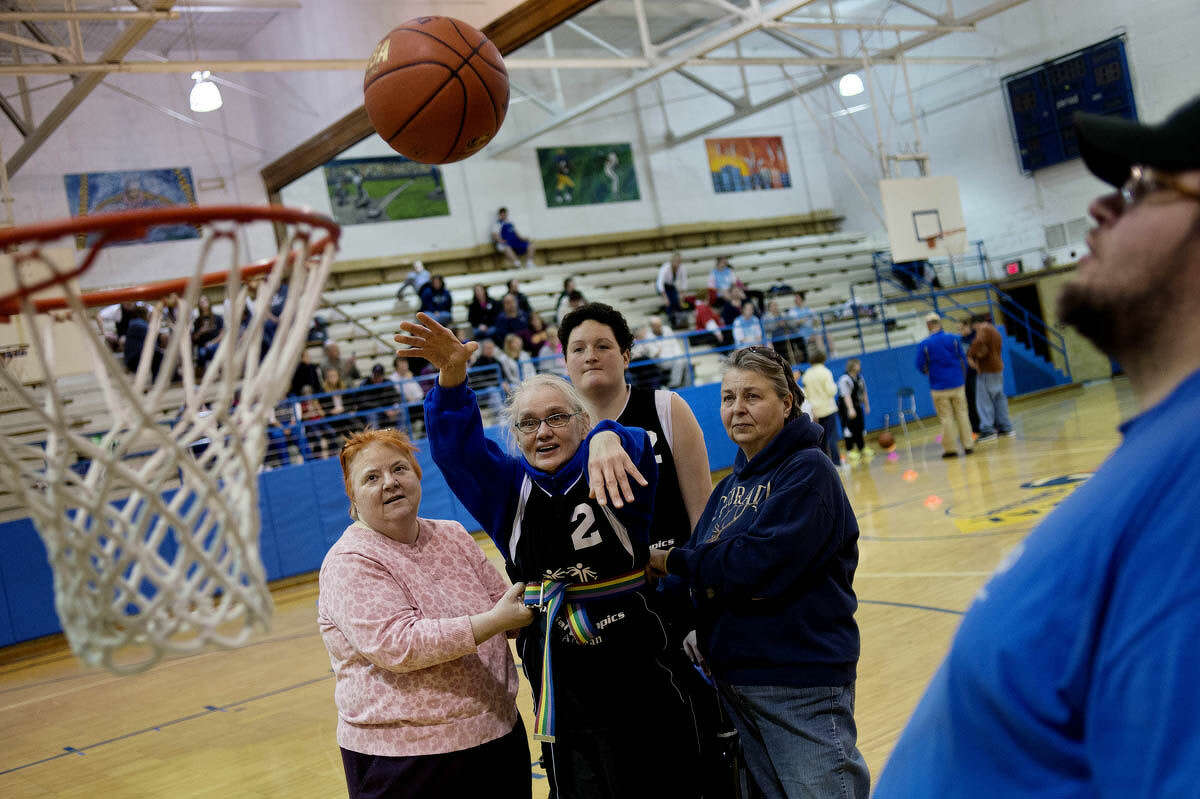 Special Olympian athlete Jenny Myer, center, shoots a basket as coach Joann Roy, left, caregiver and friend Carolyn Randall, right, and fellow athlete Nicole Fiting, back, center, look on during the sixth annual Special Olympics Regional Basketball Skills Tournament on Friday at Central Middle School. Coach Mike Logsdon, far right, looks on as well.