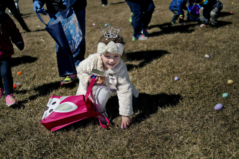 Adrianna Hair, 4, of Bay City, picks up an Easter egg during the Auburn Jaycees Easter Egg Hunt on Saturday at Auburn City Park. Adrianna, who wore her tiara from her Miss Auburn/Midland's Princess title she won in September, participated in the event with her friends Lilliana Wardell, 3, and Tori Myers, 4. The hunt was separated into four sections for age groups 10 and under. In addition to the hunt, the event featured free crafts, games, a raffle and an appearance from the Easter Bunny. Photo: Nick King/Midland  Daily News