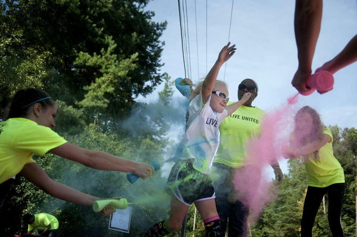 BRITTNEY LOHMILLER | for the Daily NewsVolunteers spray colored cornstarch on runners participating in the Midland County United Way 5K run on Saturday.