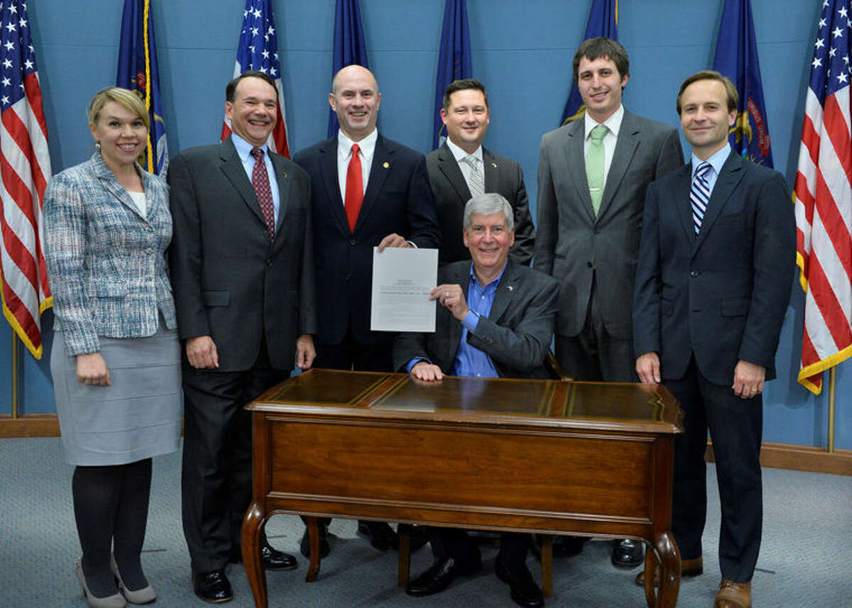Gov. Rick Snyder, seated, has signed state Rep. Gary Glenn's first bill into law, legislation in a reform package that revamps Michigan's civil asset forfeiture laws to protect citizens' property rights and civil liberties. Accompanying Glenn at the bill signing were Mackinac Center for Public Policy staff. Standing, from left, are Chantal Lovell, MCPP media relations manager; MCPP President Joseph Lehman; Glenn; Michael Reitz, MCPP executive vice president; Jarrett Skorup, MCPP policy analyst; and Lt. Gov. Brian Calley.