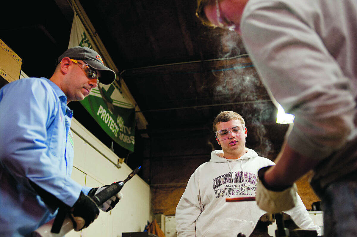 Dow Corning employee Scott Pethers and Greater Michigan Construction Academy student Colton House watch Freeland High School senior Ben Whitting solder copper fittings during a tour of the Midland Plant Wednesday morning.