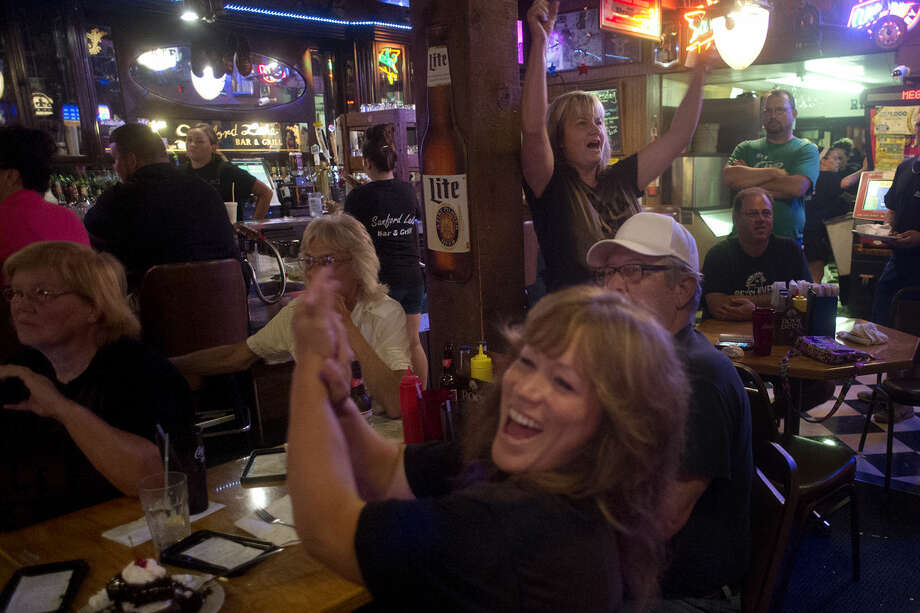 """Ruth DeFoy, left, of Harrison and Terri Lee of Hope Township celebrate Lee's daughter, Sara Lee, making it to the next round of WWE's reality television show """"Tough Enough"""" at the Sanford Bar and Grill Tuesday evening. Photo: Brittney Lohmiller 