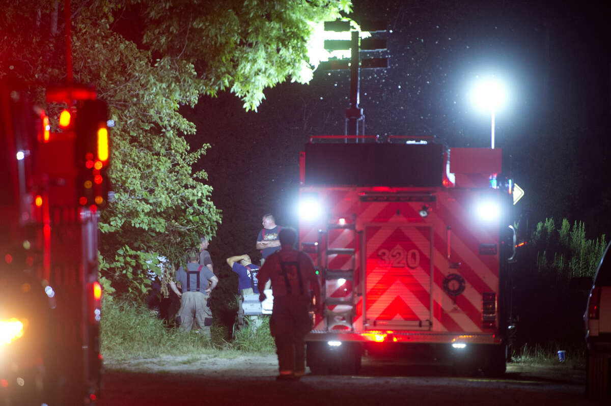 Members of the Lee and Homer Township fire departments investigate a car accident that occurred in Lee Township at the end of South 9 Mile Road Tuesday evening.