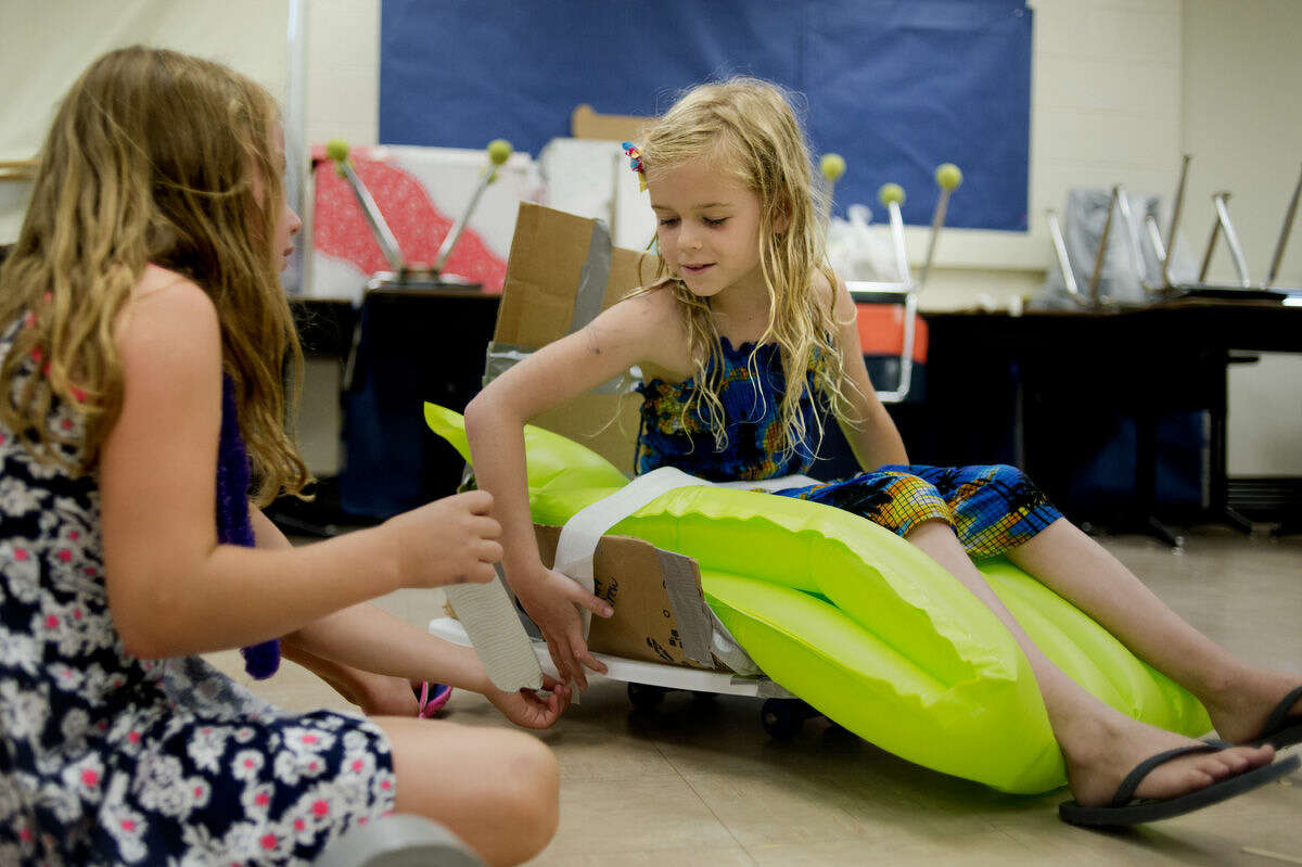 Third-graders Nicole Giardina, left, and Delaney Kepsel work on building a cart to race during the KartWheel module at Camp Invention.