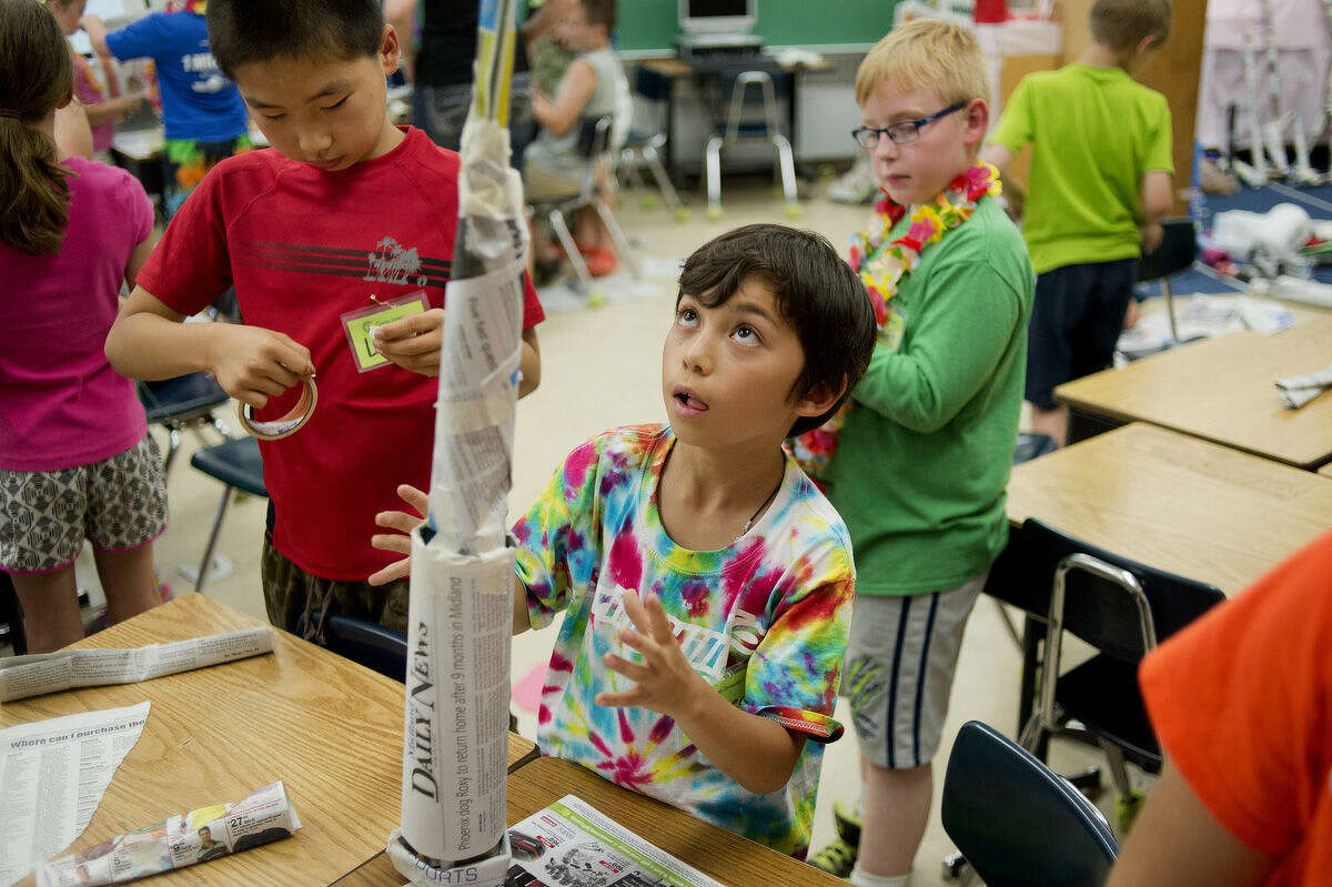 A student balances a tower built out of newspaper during a challenge event at last year's Camp Invention at Adams Elementary School.