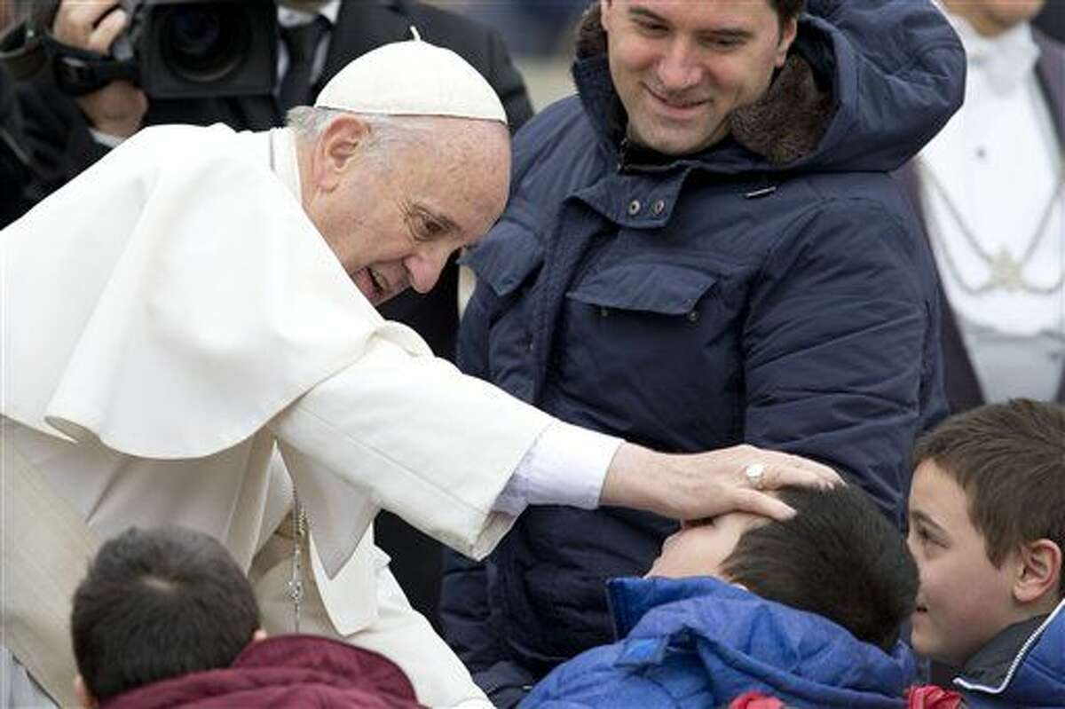 """Pope Francis blesses sick children during his weekly general audience, in St. Peter's Square, at the Vatican, Wednesday. The Vatican is denying a report in an Italian newspaper that Pope Francis has a small, curable brain tumor. The Vatican spokesman, the Rev. Federico Lombardi, said the report Wednesday in the National Daily was """"unfounded and seriously irresponsible and not worthy of attention."""""""
