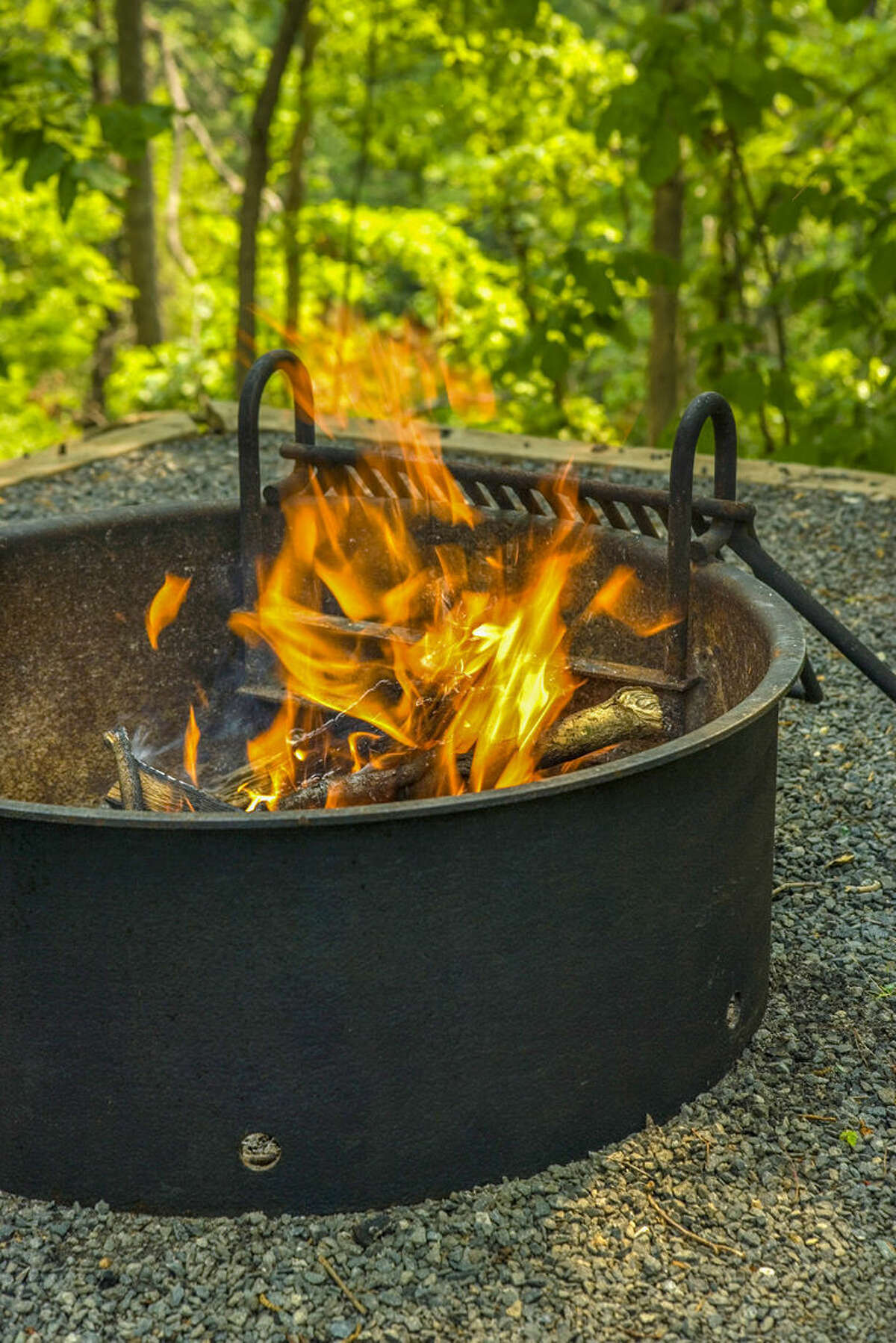 A fire pit should be at least 10 feet away from any structure or combustible surface. Unless the owner's manual says it's OK, do not put a fire pit on grass, a wood deck or in an enclosed deck/porch.