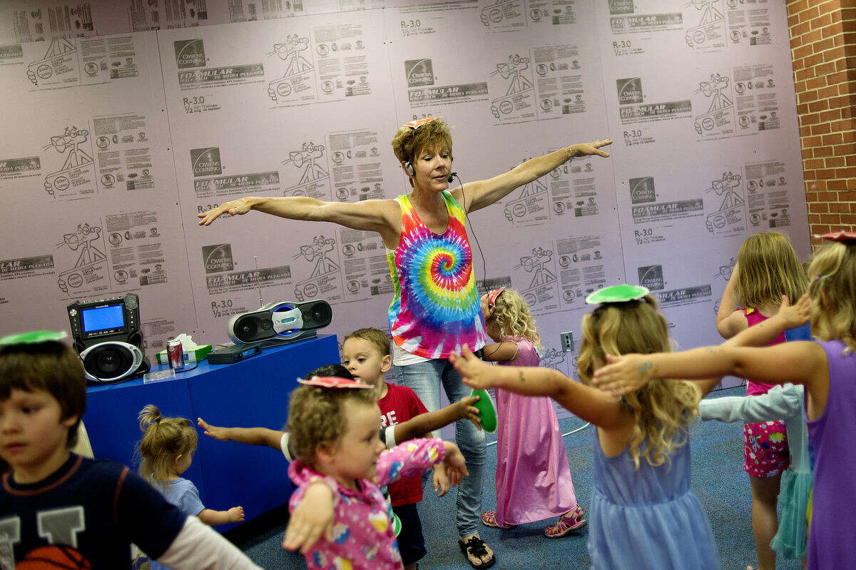 Rebecca Anlas sings and dances along with kids as they perform various motions with different colored bean bags during the Pajama Jams event on Monday at the Grace A. Dow Memorial Library.