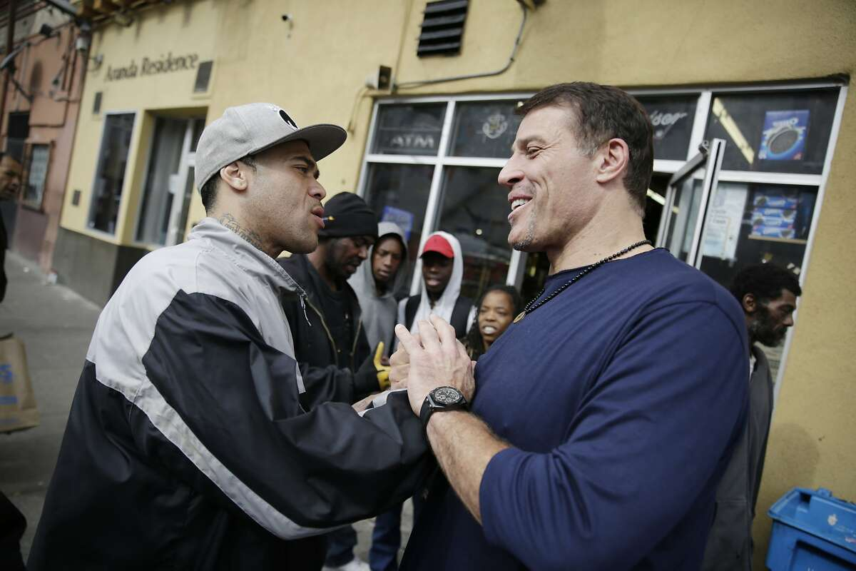 Tony Robbins (right), motivational speaker and author, is greeted by Mariano Fernandez (right) of San Francisco after Robbins was spotted by locals as he left Fraternite Notre Dame Mary of Nazareth Soup Kitchen after visiting with Sister Mary Valerie and Sister Mary Benedicte (both not shown) to discuss solutions to their eviction on Thursday, February 11, 2016 in San Francisco, Calif.