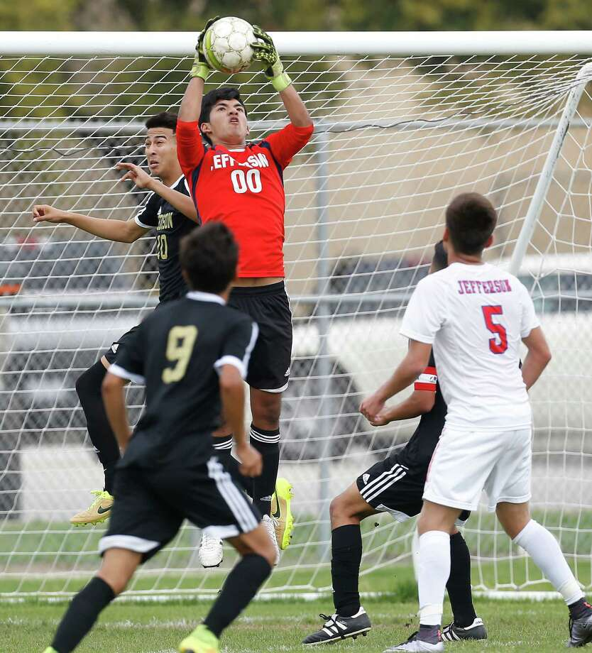 Jefferson goalkeeper Miguel Del Fierro makes a save against Edison's Livan Hernandez (20) in a boys soccer match to determine the District 28-5A championship title at SAISD Spring Sports Complex on Thursday, Mar. 17, 2016. Jefferson won the title but both teams will head into playoffs. The Mustangs defeated the Bears, 4-1. (Kin Man Hui/San Antonio Express-News) Photo: Kin Man Hui, Staff / San Antonio Express-News / ©2016 San Antonio Express-News