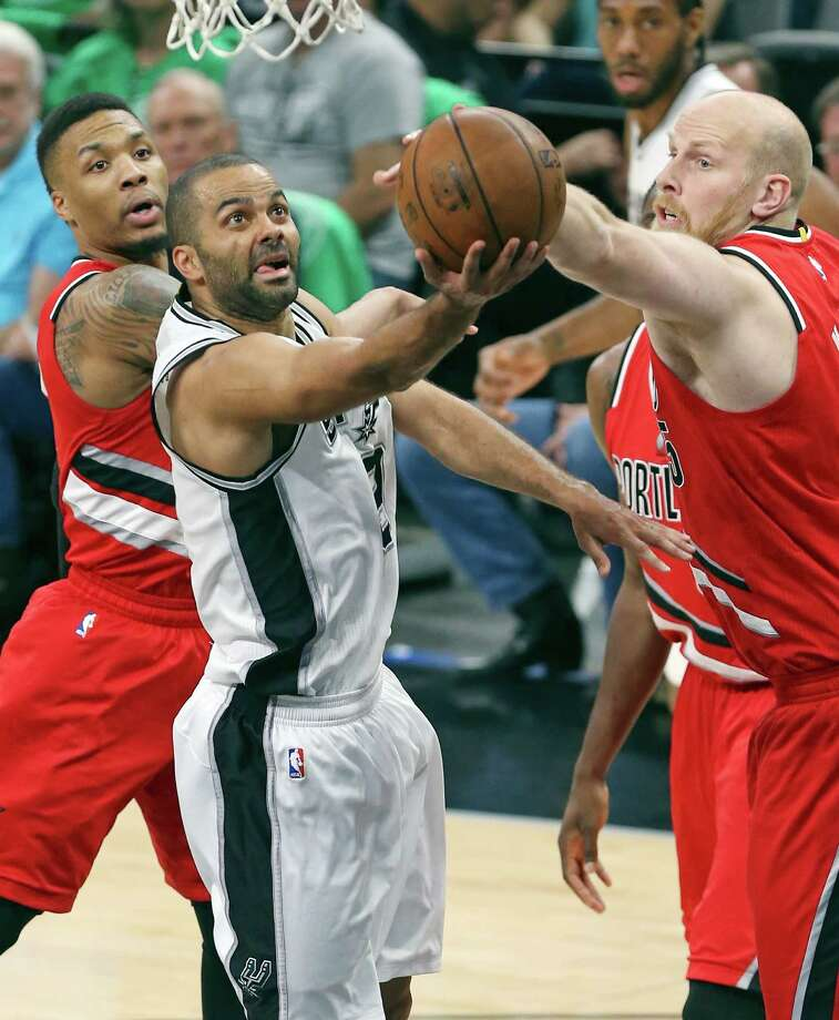 San Antonio Spurs' Tony Parker shoots between Portland Trail Blazers' Damian Lillard (left) and Chris Kaman during first half action Thursday March 17, 2016 at the AT&T Center. Photo: Edward A. Ornelas, San Antonio Express-News / © 2016 San Antonio Express-News