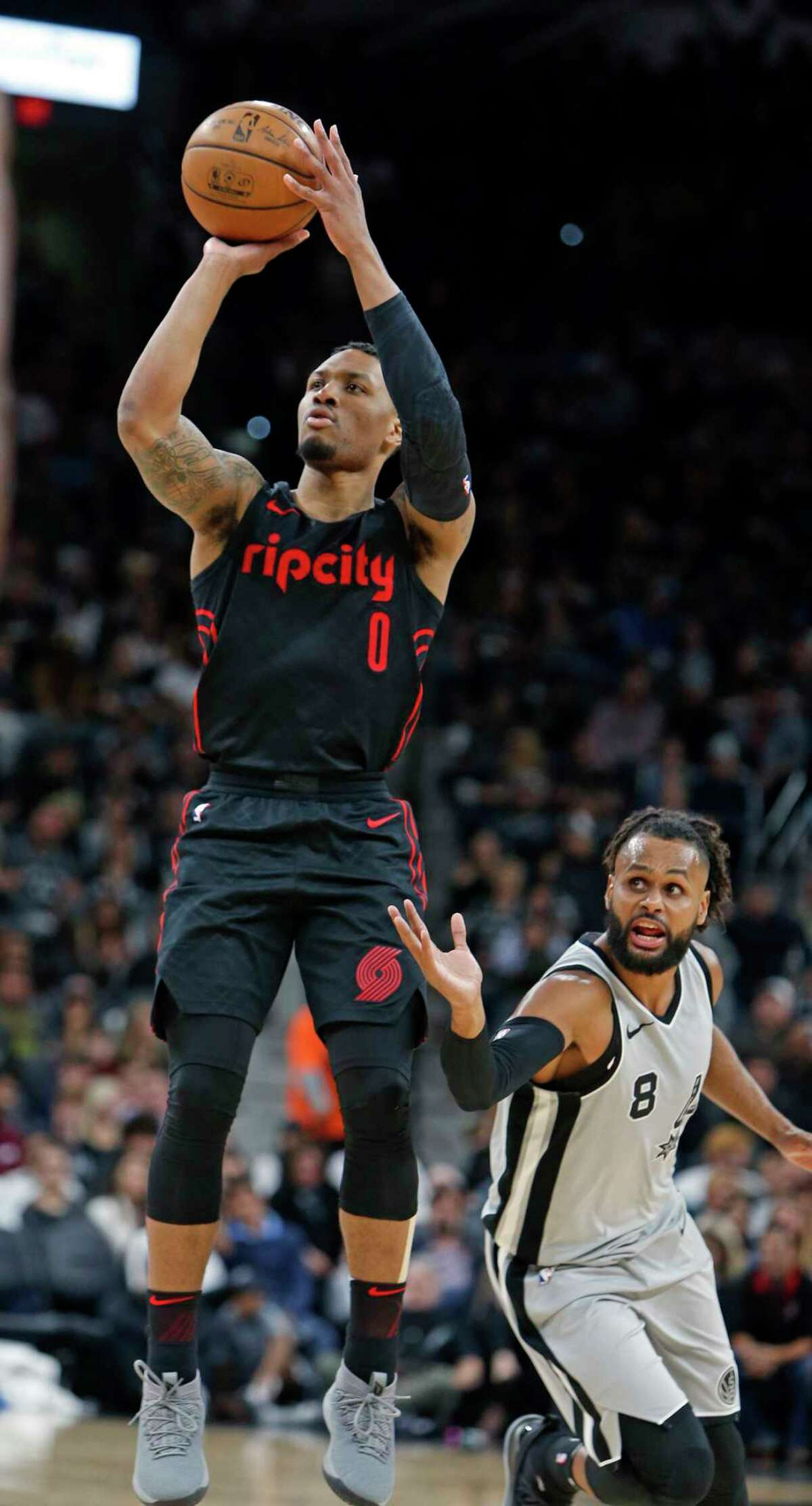 Portland Trail Blazers point guard Damian Lillard (0) shoots in front San Antonio Spurs guard Patty Mills (8) during the first half of an NBA basketball game Saturday, April 7, 2018, in San Antonio. (AP Photo/Ronald Cortes)