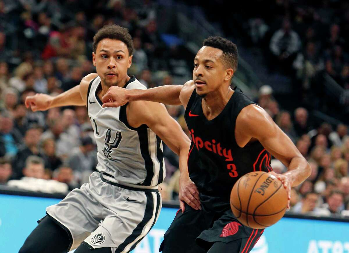 Portland Trail Blazers shooting guard C.J. McCollum (3) drives on San Antonio Spurs guard Bryn Forbes (11) during the first half of an NBA basketball game Saturday, April 7, 2018, in San Antonio. (AP Photo/Ronald Cortes)