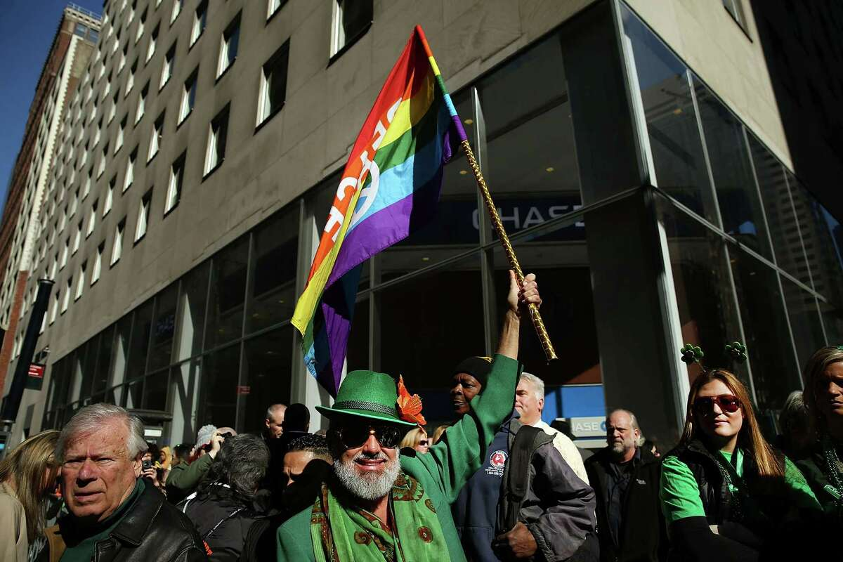 NEW YORK, NY - MARCH 17: A man holds up a Gay Pride flag at the annual St. Patrick's Day parade, one of the largest and oldest in the world on March 17, 2016 in New York City. Now that a ban on openly gay groups has been dropped, New York Mayor Bill de Blasio is attending the parade for the first time since he became mayor in 2014. The parade goes up Fifth Avenue ending at East 79th Street and will draw an estimated 2 million spectators along its 35-block stretch. (Photo by Spencer Platt/Getty Images) ORG XMIT: 611140611