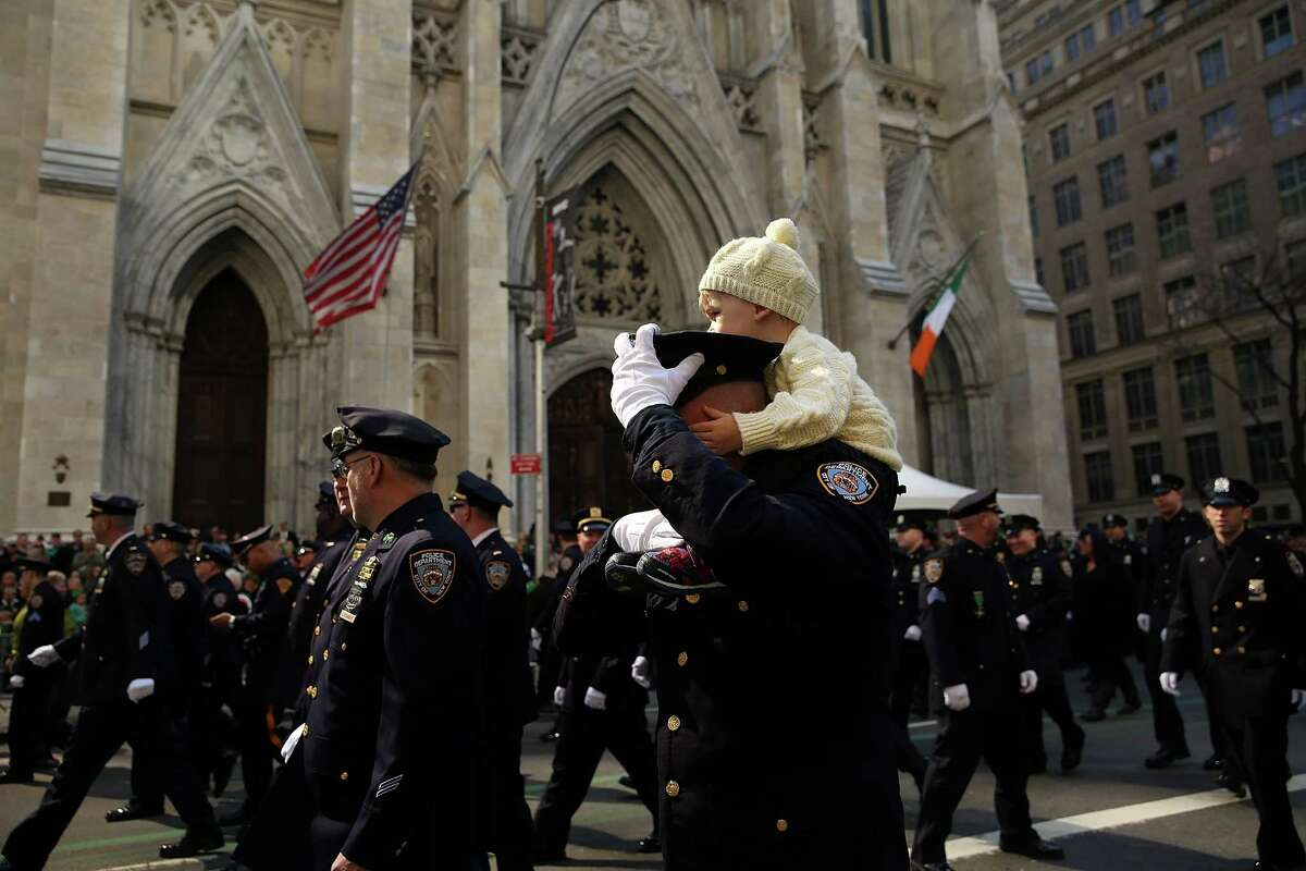 NEW YORK, NY - MARCH 17: A police officer and his son march in the annual St. Patrick's Day parade, one of the largest and oldest in the world on March 17, 2016 in New York City. Now that a ban on openly gay groups has been dropped, New York Mayor Bill de Blasio is attending the parade for the first time since he became mayor in 2014. The parade goes up Fifth Avenue ending at East 79th Street and will draw an estimated 2 million spectators along its 35-block stretch. (Photo by Spencer Platt/Getty Images) ORG XMIT: 611140611