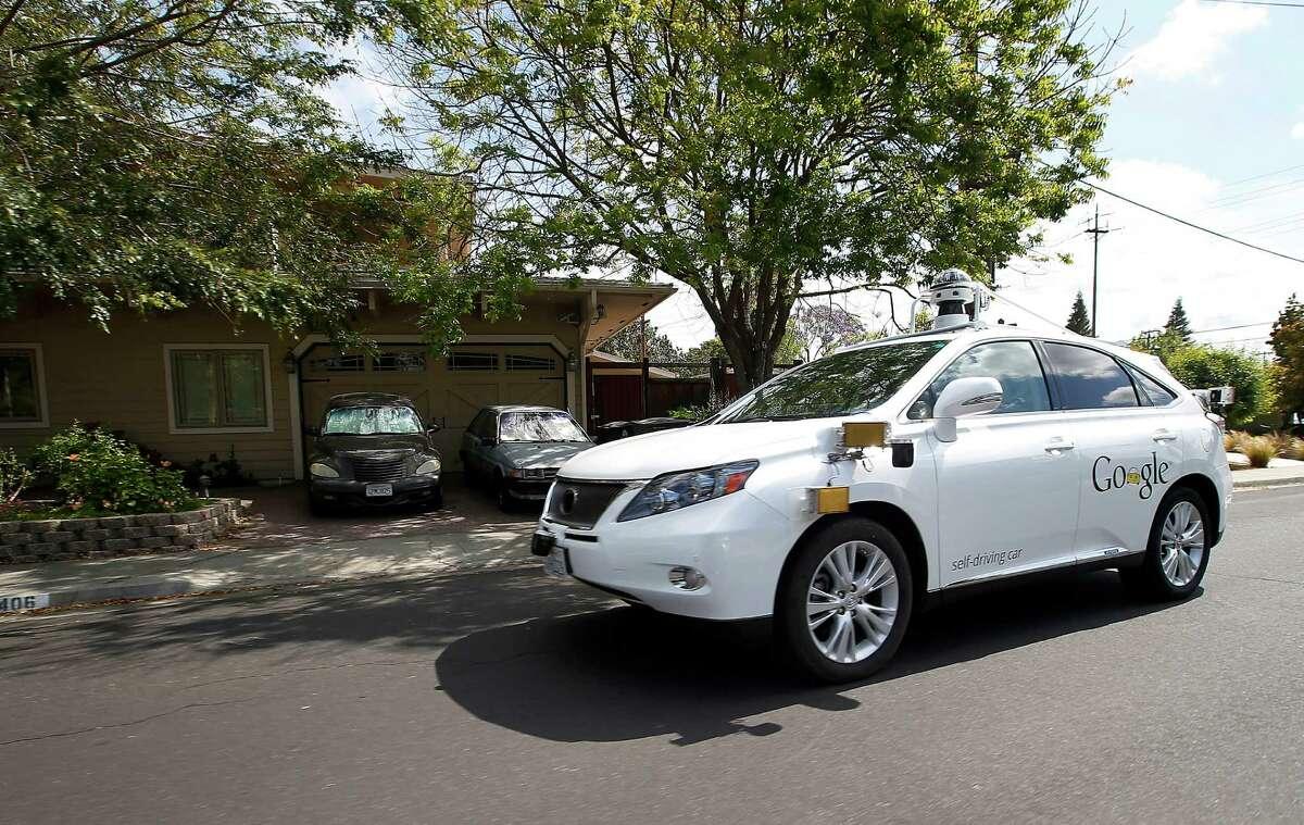 A Google self-driving Lexus cruises along a street in Mountain View, Calif.