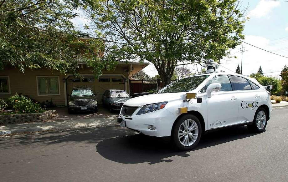 A Google self-driving Lexus cruises along a street in Mountain View, Calif. Photo: Tony Avelar, FRE