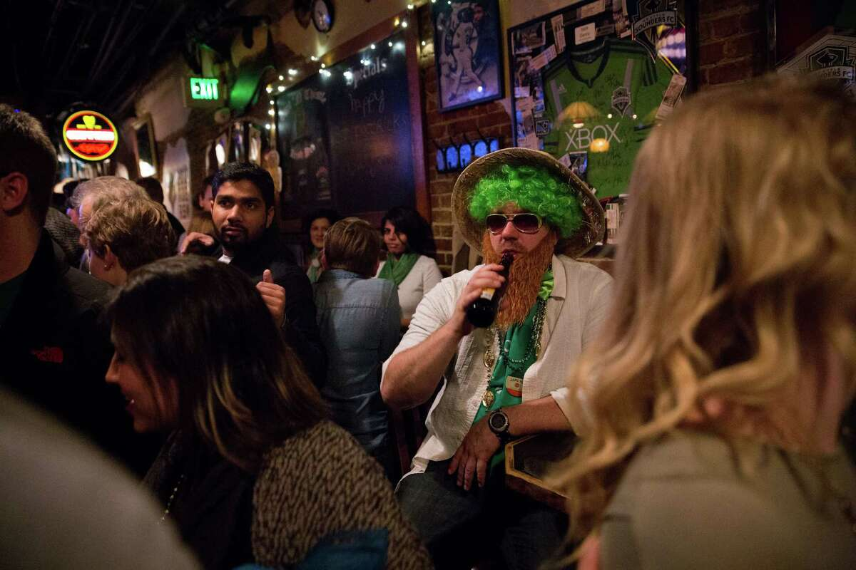 A costumed man peers into the crowd at Owl N' Thistle on St. Patrick's Day, Thursday, Mar. 17, 2016.