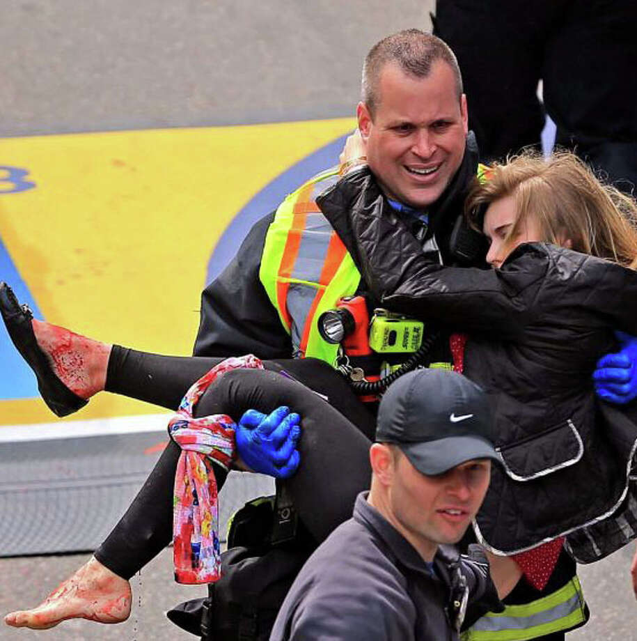 Victoria McGrath, a Northeastern University student from Weston, was helped by emergency personnel after she was injured by explosions near the finish line at the Boston Marathon on April 15, 2013. Photo: Boston Globe / David L. Ryan / Westport News