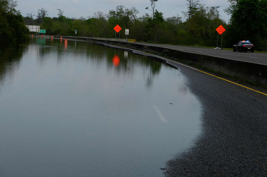 Water covers the westbound lanes of Interstate 10 near the Simmons Drive exit in Orange on Thursday afternoon. It's unknown when the highway will reopen, as Texas Department of Transportation needs to inspect for damages once water recedes.  Photo taken Thursday 3/17/16 Ryan Pelham/The Enterprise Photo: Ryan Pelham / ©2016 The Beaumont Enterprise/Ryan Pelham