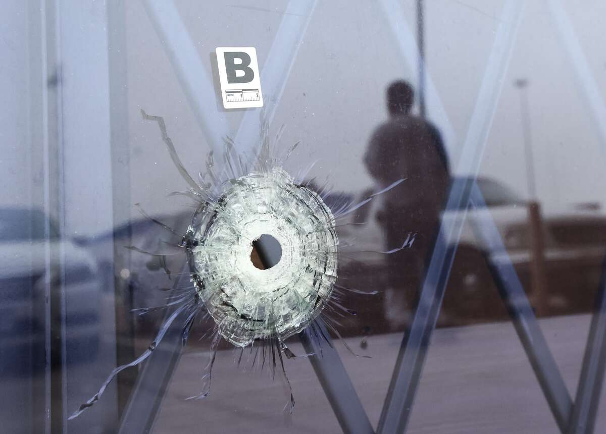 A bullet hole is seen at an Affordable Furniture store in the 11300 block of the North Freeway, the morning after Houston Police shot and killed two people and injured a third when they confronted a group of five men during an alleged robbery, Friday, March 18, in Houston. ( Jon Shapley / Houston Chronicle )