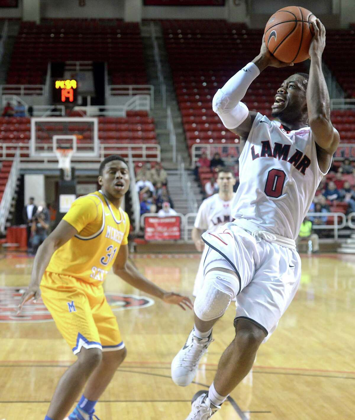Lamar's Kevin Booze puts up his shot after skirting around McNeese's defense during Monday night's match-up at the Montagne Center. The rivalry also marks the Cardinals' final home game of the season. Photo taken Monday, February 29, 2016 Kim Brent/The Enterprise