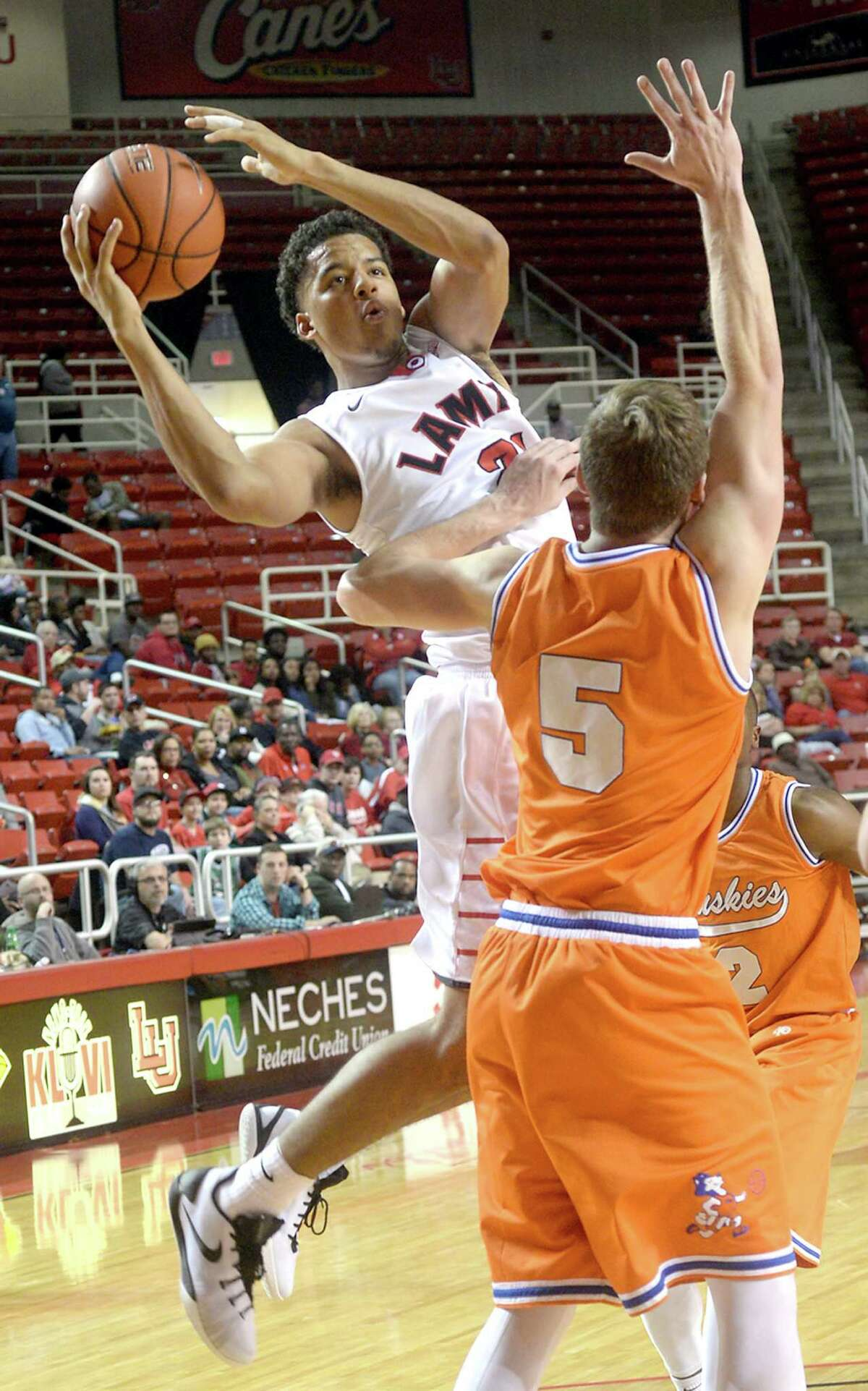 Lamar's Boaz Williams looks to shoot over the pressure of Houston Baptist's Colter Lasher during Saturday's match-up at the Montagne Center. Photo taken Saturday, January 23, 2016 Kim Brent/The Enterprise