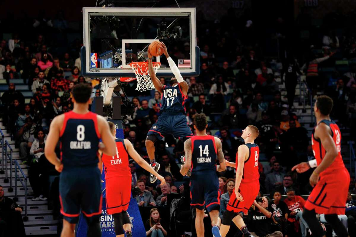 U.S. Team guard Jonathon Simmons of the San Antonio Spurs (17) slam dunks in front of World Team guard Danté Exum of the Utah Jazz (11) and Nikola Jokic of the Denver Nuggets (15) during the Rising Stars Challenge as part of the NBA All Star festivities in New Orleans, Friday, Feb. 17, 2017. (AP Photo/Gerald Herbert)
