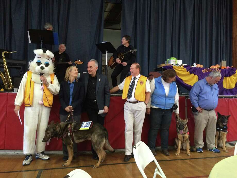 At the Pancake Fry, the Greenwich Lions gave its annual gift to Fidelco to help its efforts getitng guide dogs to people who need them. From left: Easter Bunny and co-Lions president Paul Settlemeyer, Nancy Lothrop, general manager of Fidelco, Eliot Russman executive director of Fidelco, Deb O'Brien, Fidelco puppy raiser; Dave Bonney, Lions co-president and Eric Gardell, a Fidelco trainer. Photo: / Contributed Photo