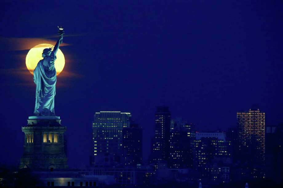 A full moon rises behind the Statue of Liberty seen from the Port Liberte neighborhood of Jersey City, N.J. With all the presidential talk about deporting or banning immigrants from our shores, a reader wonders if the statue has any meaning any more. Photo: Julio Cortez /AP / AP