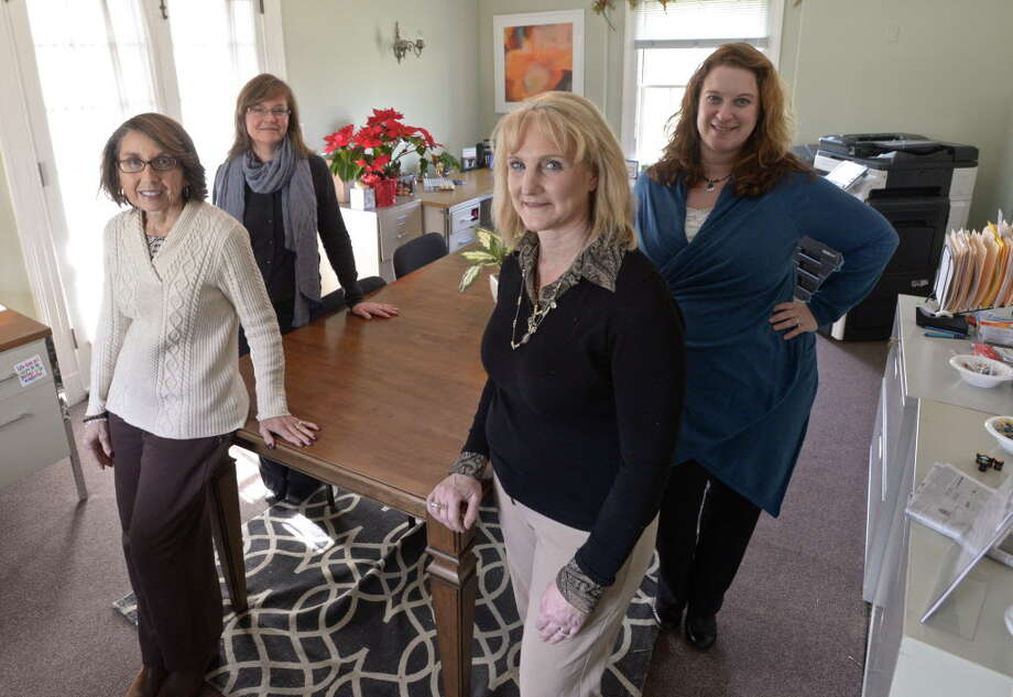 Four of the six members of the Newtown Recovery and Resiliency Team (R&R Team) in their office is on the Fairfield Hills Campus, in Newtown, Conn. December 31, 2015. Deb DelVecchio-Scully, front left, clinical recovery leader, Melissa Glaser, front right, community outreach liaison,  Catherine Galda, back left, case coordinator, and Margot Robins, back right, project manager. Photo: H John Voorhees III / Hearst Connecticut Media / The News-Times