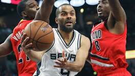 Tony parker gets to the hoop but passes away from faked out defenders Noah Vonleh and Al-Farouq Aminu as the Spurs host the Blazers at the AT&T Center  on March 17, 2016.