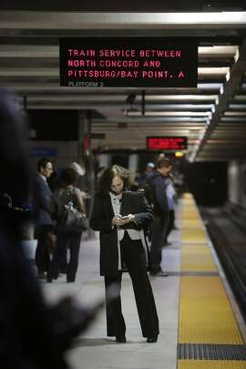 Jenny Wodinsky of Orinda stands under a sign alerting riders to a bus bridge between the North Concord and Pittburgh/Bay Point  station as she waits for the Pittburgh/Bay Point Bart train at Embarcadero Station on Friday, March 18, 2016 in San Francisco, California.